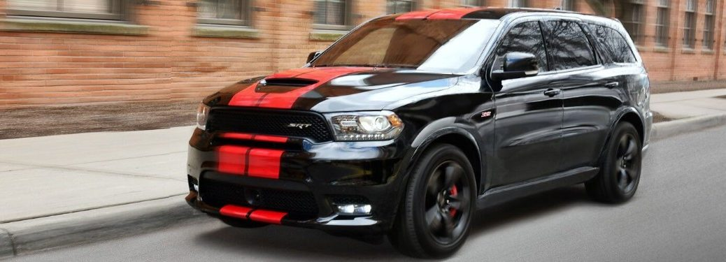 Front driver angle of a black 2019 Dodge Durango with red stripes driving down a road