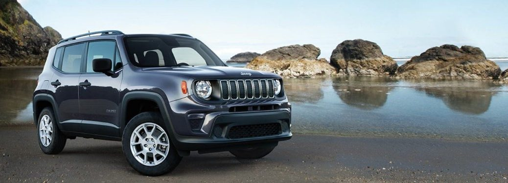 Front passenger angle of a blue 2019 Jeep Renegade parked on a beach with large rocks in the water