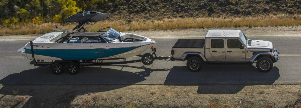 2020 Jeep Gladiator passenger side towing boat on country highway