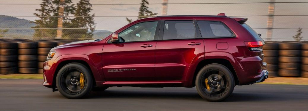 2020 Jeep Grand Cherokee red exterior driver side driving past stacks of tires