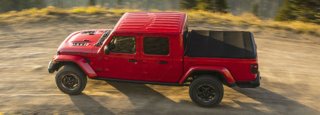 2020 Jeep Gladiator red exterior sky view of driver side driving on gravel road