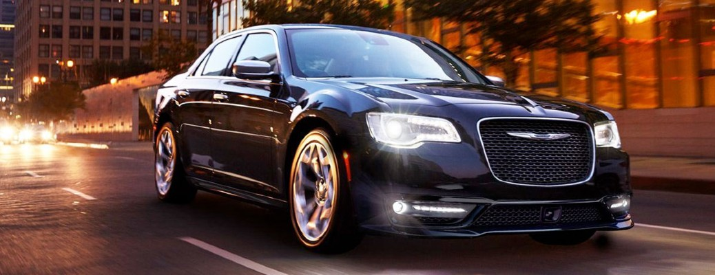 2020 Chrysler 300 black exterior front passenger side driving in city at night headlights on