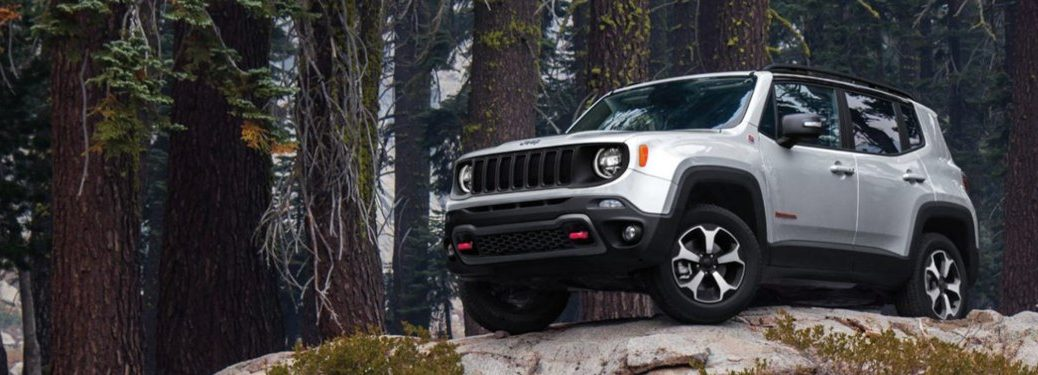 2020 Jeep Renegade white exterior front driver side parked on top of cliff in forest