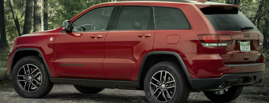 A red-colored 2021 Jeep Grand Cherokee parked outside near the woods