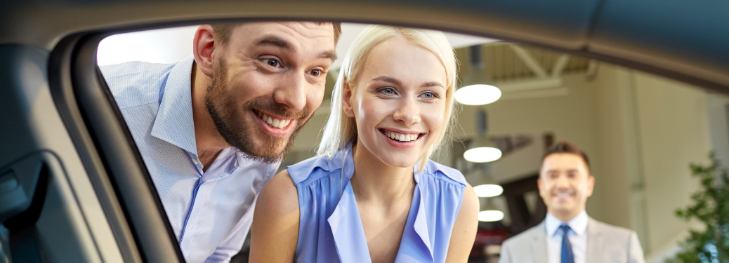 couple looking in car window at dealership