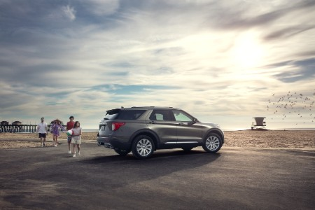 Rear passenger angle of a silver 2020 Ford Explorer parked on a beach with a family walking towards it