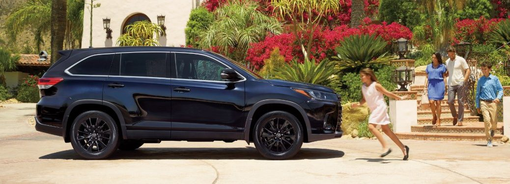 Passenger angle of a dark blue 2019 Toyota Highlander parked in front of a home with a girl running to it and her family walking behind her