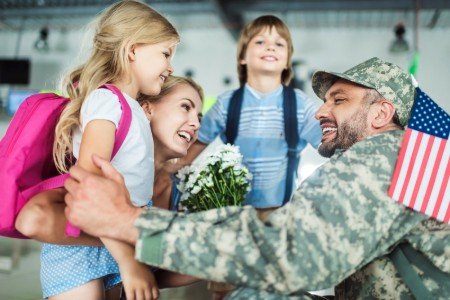 Military dad in uniform with his happy family