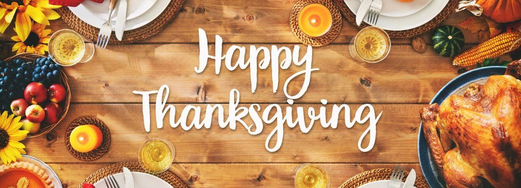 "Wood background with food surrounding the text ""Happy Thanksgiving"""