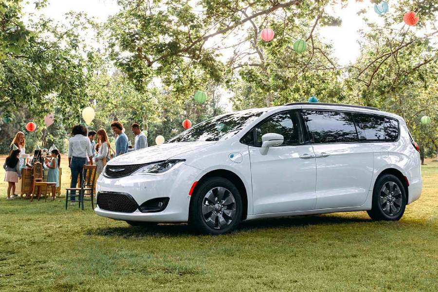 Front driver angle of a white 2020 Chrysler Pacifica parked by an outdoor party