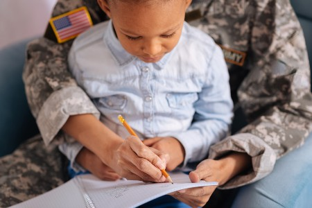 Boy writing a letter with a soldier helping him write