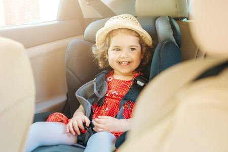 Happy little girl sitting in a car seat