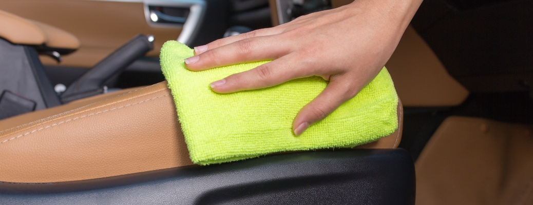 Cleaning a leather seat with a yellow microfiber cloth