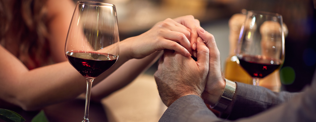 Couple holding hands with wine