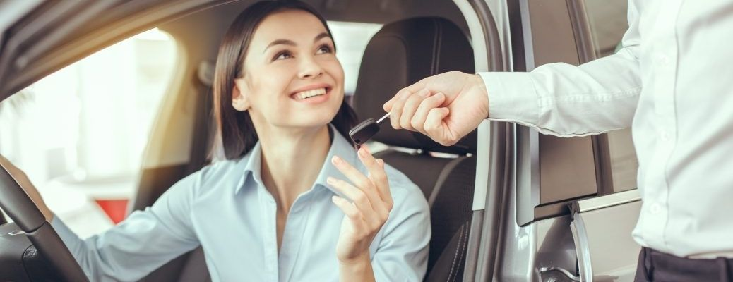 Woman accepting key from dealer agent