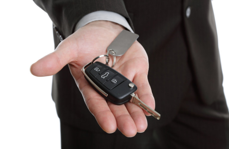 Hand holding out keys to new vehicle