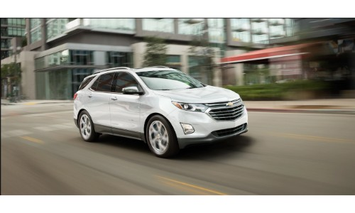 2019 Chevy Equinox exterior shot with white paint color driving through a city as the background blurs