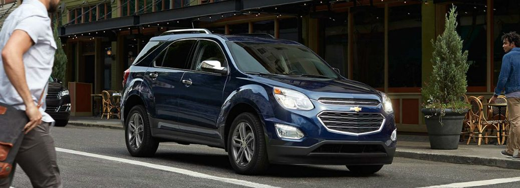 Blue 2017 Chevrolet Equinox rolls down a city street as onlookers look on in awe.