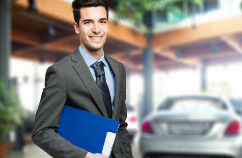 A smiling salesman holds a blue folder with a blurry car in the background.