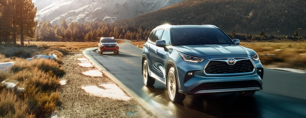 Two 2020 Toyota Highlander SUVs going down the road with mountains in the background
