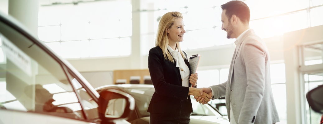 Woman and man shaking hands at a car dealership