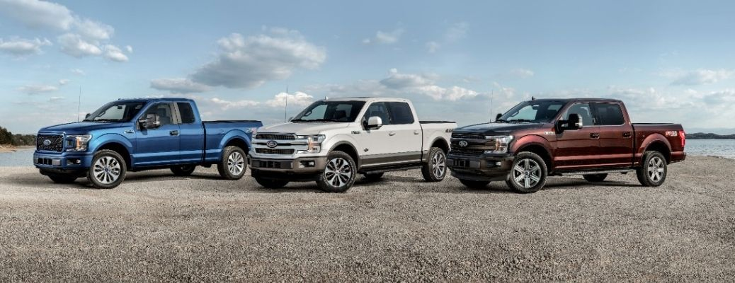 Side quarter view of three Ford F-150 models parked next to each other against the blue sky
