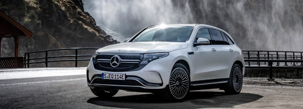 mercedes-benz eqc parked next to a waterfall