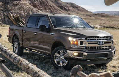 2019 Ford F-150 exterior front fascia and passenger side in wilderness with cargo in bed of truck