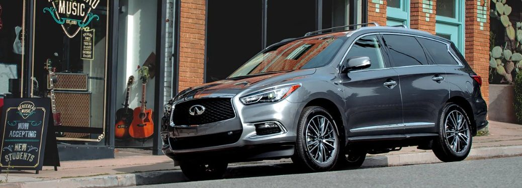 Front driver angle of a grey 2020 INFINITI QX60 parked in front of a music store