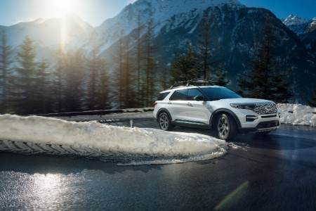 Far shot of a white 2020 Ford Explorer taking a turn on a wet road with snow on the grass