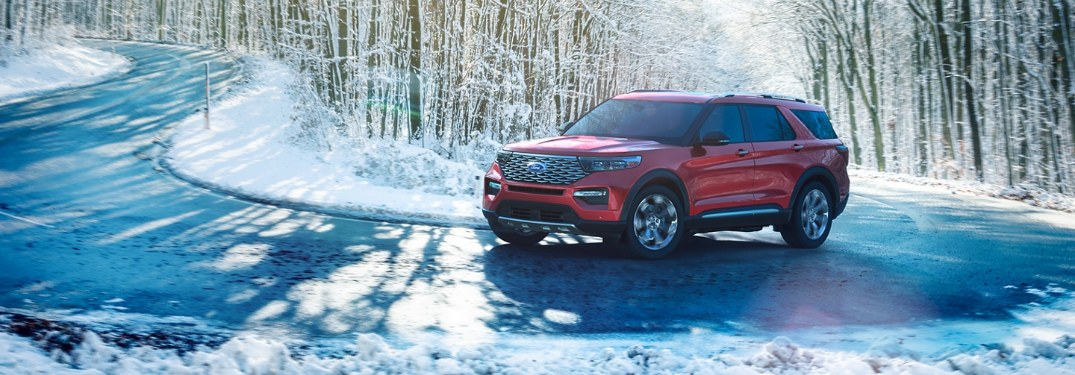 Front driver angle of a red 2020 Ford Explorer driving on a curvy and snowy road