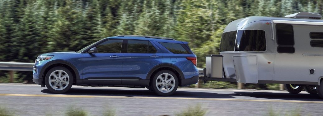 Driver angle of a blue 2020 Ford Explorer towing a trailer