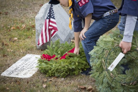 Boy scout placing a wreath at a veteran's grave