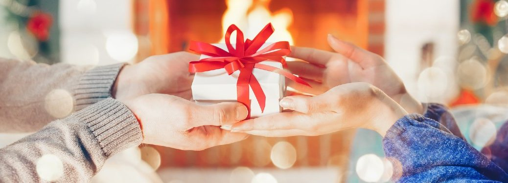 Close up of a person gifting a present to another with a fireplace in the background