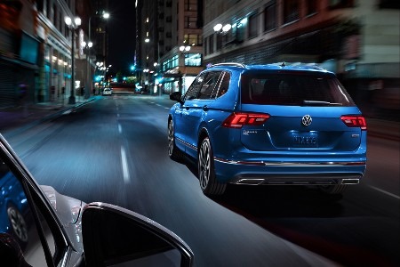 Rear driver angle of a blue 2020 Volkswagen Tiguan driving on a road at night
