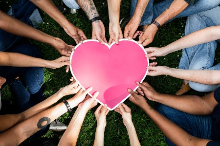 Multiple people holding a pink heart
