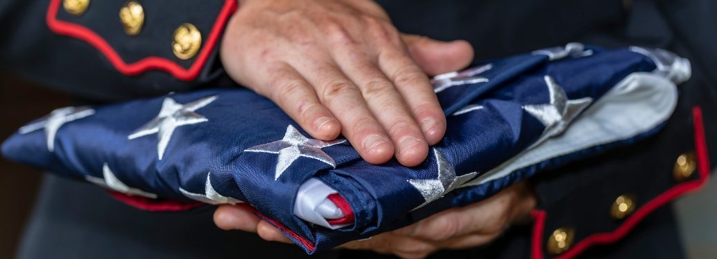 Close up of a marine holding a folded American flag
