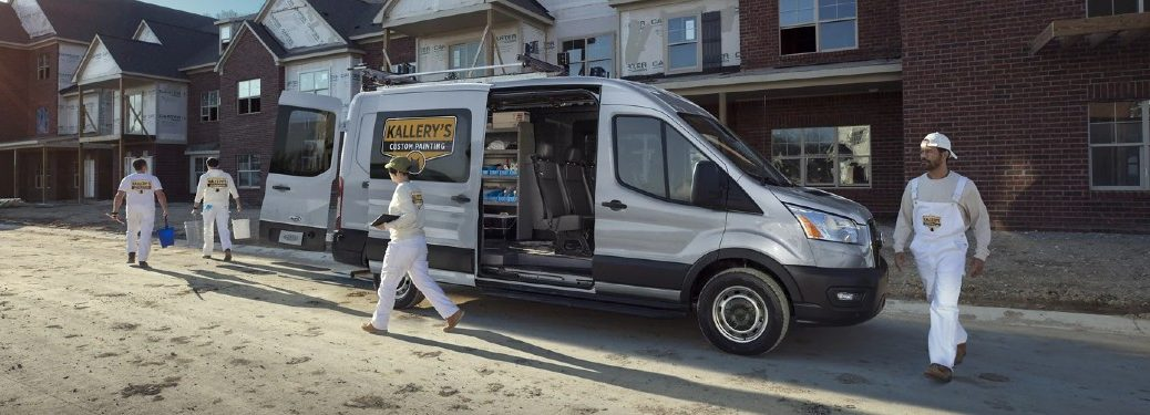 Workers working around a white 2021 Ford Transit