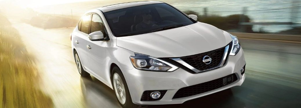 Front passenger angle of a white 2019 Nissan Sentra driving down a road