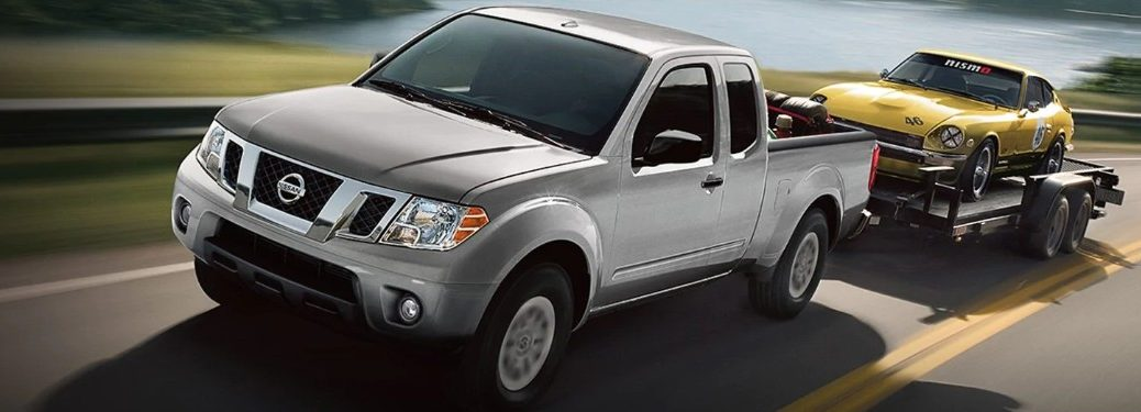 Front driver angle of a grey 2019 Nissan Frontier pulling a trailer with a yellow car loaded