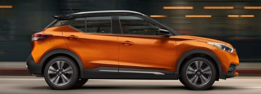 Passenger angle of an orange 2019 Nissan Kicks driving with a blurry background