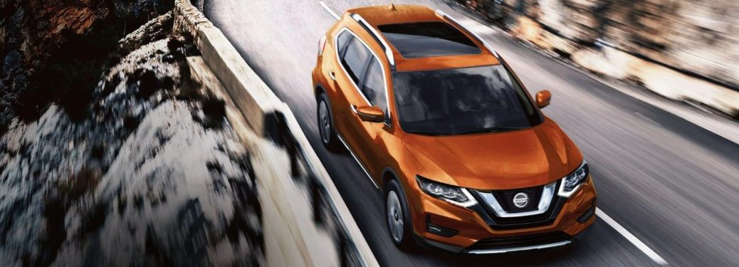 Front passenger angle of an orange 2020 Nissan Rogue driving on a road