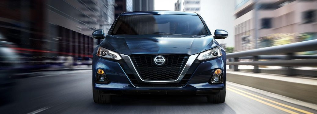 Front angle of a blue 2020 Nissan Altima driving in a city