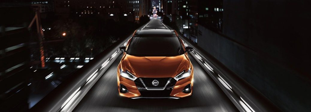 Front angle of an orange 2020 Nissan Maxima driving down a city street at night