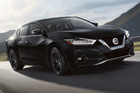 Front passenger angle of a black 2020 Nissan Maxima driving on a road