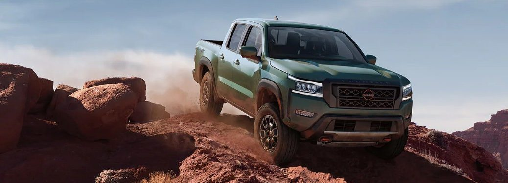 Front passenger angle of a green 2022 Nissan Frontier off-roading