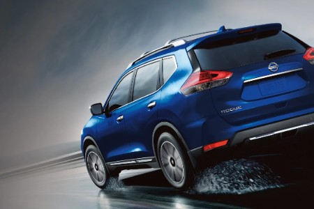 Rear driver angle of a blue 2019 Nissan Rogue driving on a wet road