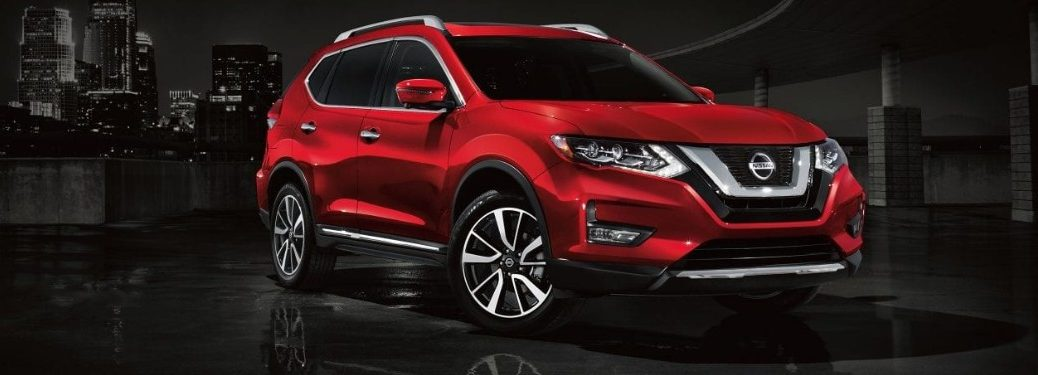 Front passenger angle of a red 2019 Nissan Rogue on a dark city background