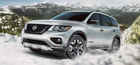 Front driver angle of a silver 2020 Nissan Pathfinder driving on a snowy mountain