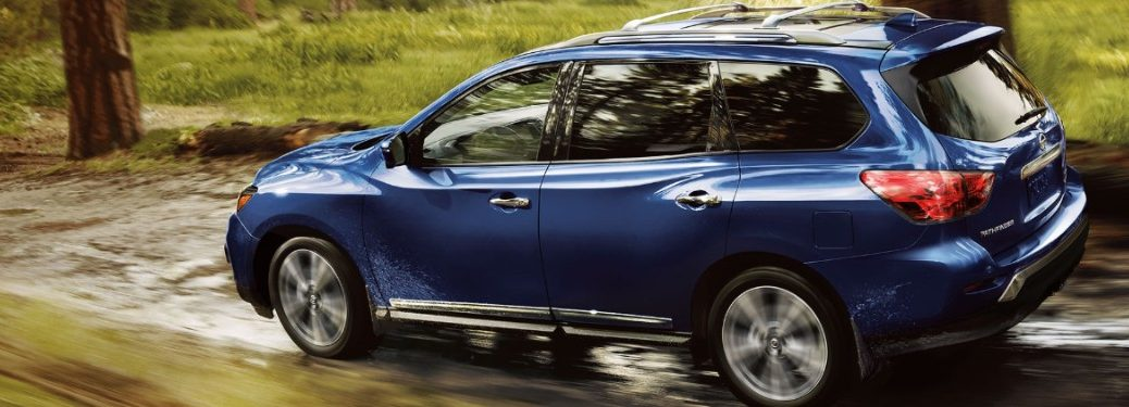 Rear driver angle of a blue 2020 Nissan Pathfinder driving through a shallow stream in the woods